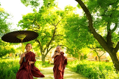 Two little Buddhist monks running outdoors under shade of green tree, outside monastery, Myanmar.