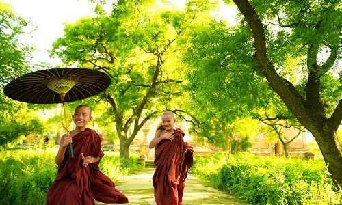 Two little Buddhist monks running outdoors under shade of green